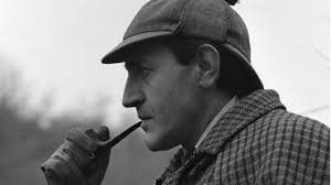 Sherlock Holmes smoking a pipe and looking pensive.
